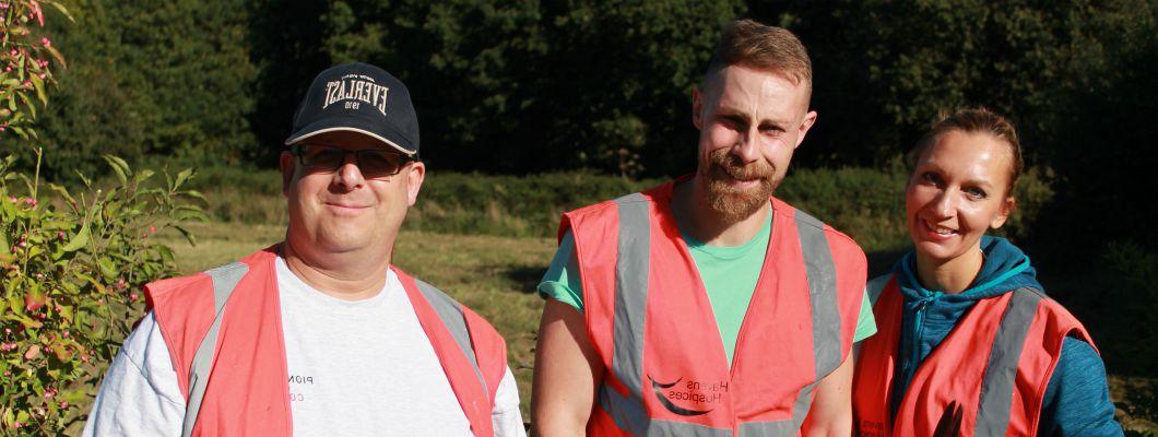 three corporate volunteers gardening