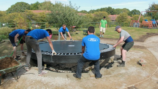 corporate volunteers installing a trampoline in the Little Havens gardens