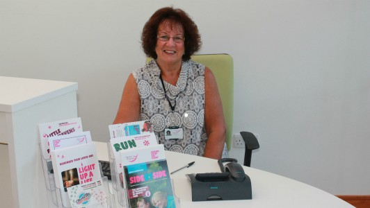 Volunteer receptionist, Fran, sitting behind a desk