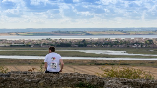 Havens to Havens Walk participant sitting on a hill looking out at the view. His race number and a photo of a loved one is pinned to the back of his t-shirt