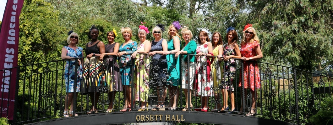 Twelve women standing on the Orsett Hall bridge smiling for a photo