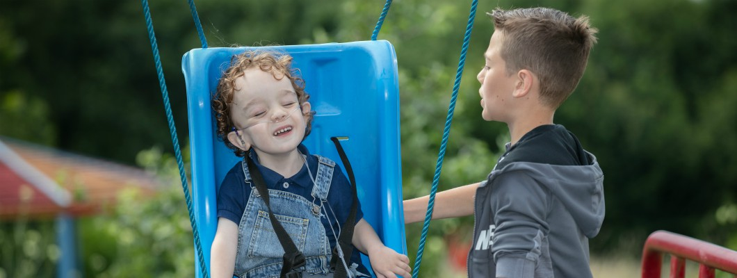 Little Havens child Miller being pushed on the swings by his older brother