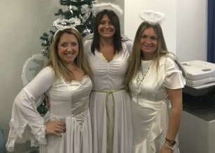 Three women dressed in angel Christmas costumes