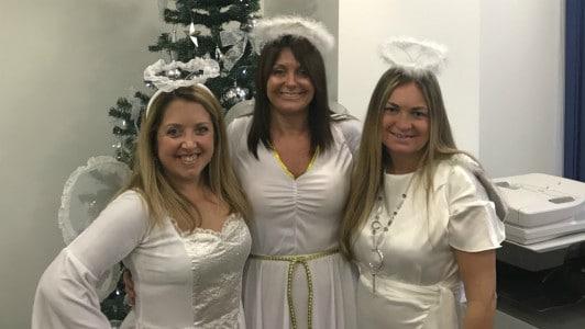 Three women in angel Christmas costumes