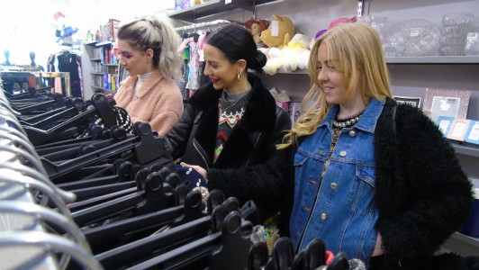 three shoppers browsing clothes rails