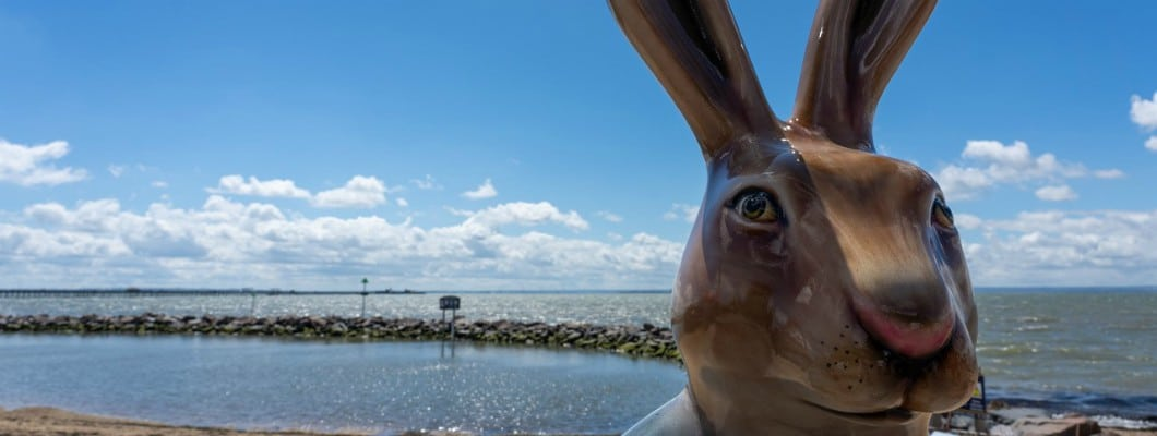 close up of Hare sculpture with the sea in the background