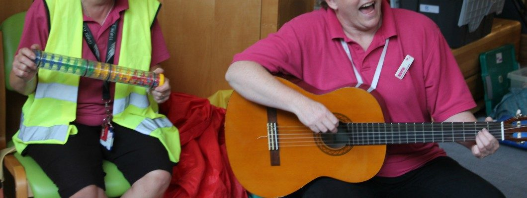 Ruth holding her guitar at sensory storytime