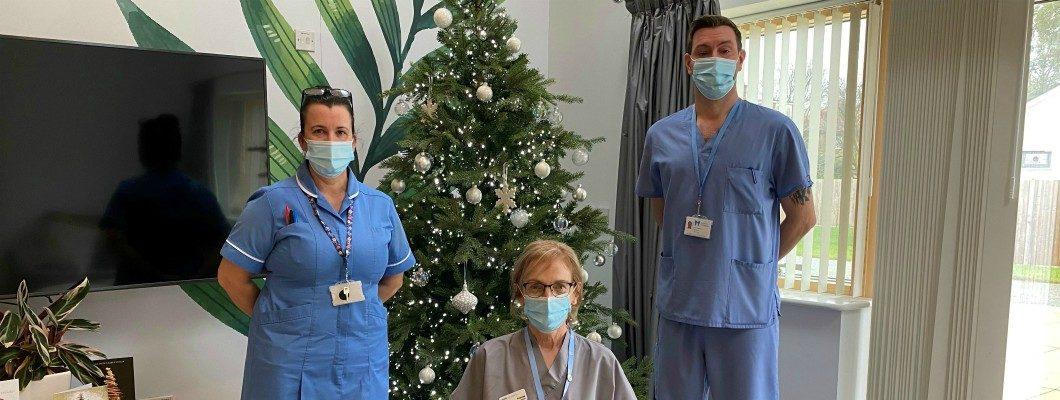 Three nurses in masks stood by christmas tree