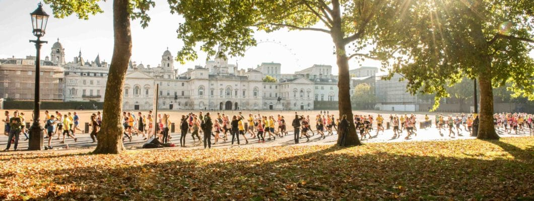 Photo of buckingham palace in the distant runners in front with leaves and trees in front of them