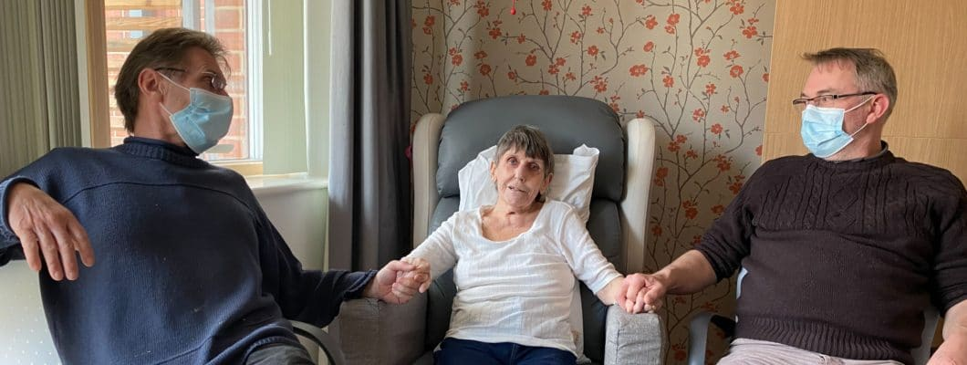 Ann sat in chair at the hospice with sons sat either side of her holding hands