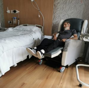 A man lying down in a recliner chair, sleeping next to a bed