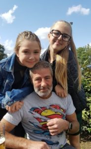 A man wearing a grey superman t-shirt looking straight at the camera. His two young daughters are cuddling him from above, looking and smiling into camera