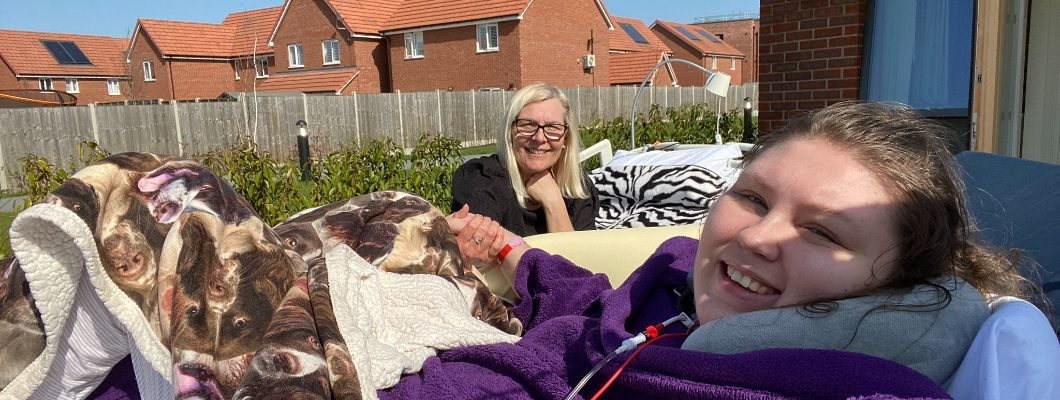Lucy in bed outside hospice garden holding hands with her mum