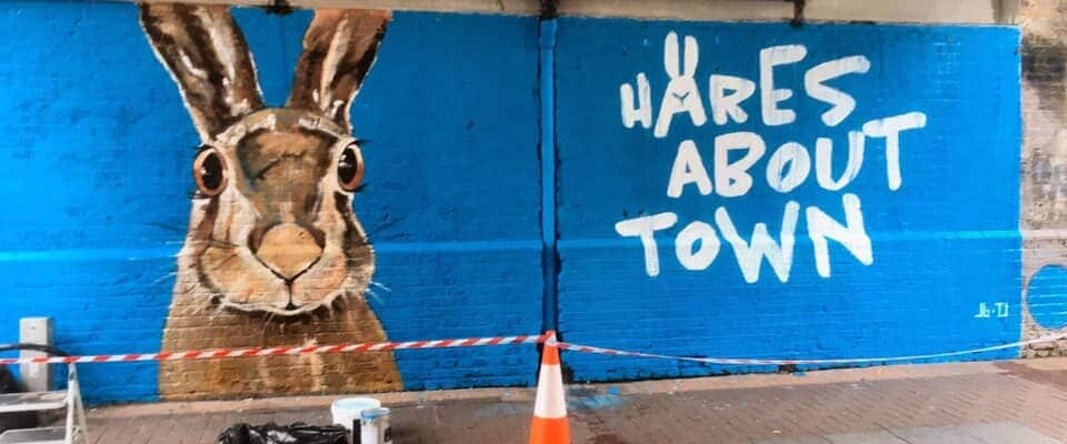 Hares About Town mural painted on wall with blue background and hare