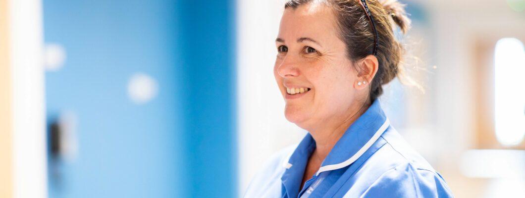 Karen nurse holding folder smiling in corridor