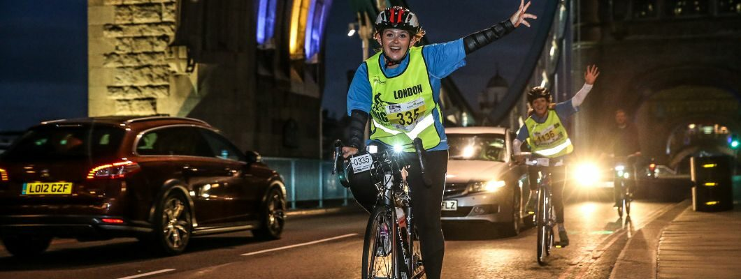 Cyclist taking part in a night ride event, raising their hand in celebration